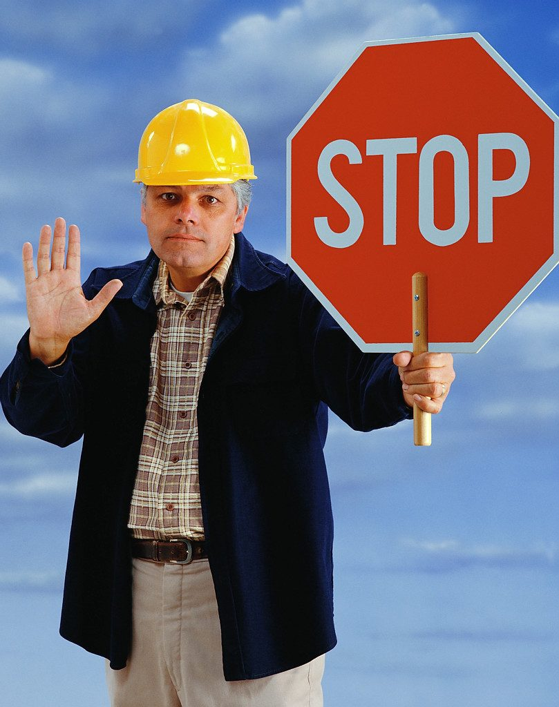 A Man In A Yellow Safety Hat Holding Up His Hand and Holding A Sign That Read STOP 809x1024 A Man In A Yellow Safety Hat Holding Up His Hand and Holding A Sign That Read STOP